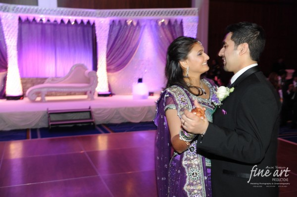 An Indian bride and groom dance at their Indian wedding reception.