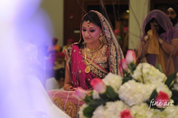 Indian bride wears a traditional bridal lengha in pink.