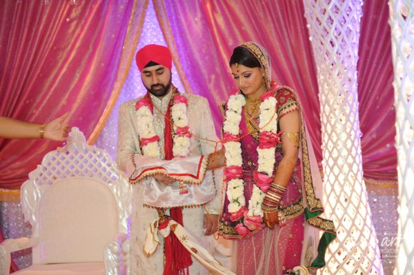 An Indian bride and groom wearing modern indian wedding wear.