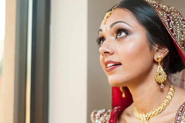 This Indian bridal makeup includes long lashes, a red lip and subtle blush.