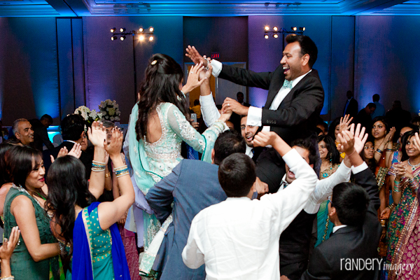 An Indian bride and groom are hoisted in the air at their Indian wedding reception.