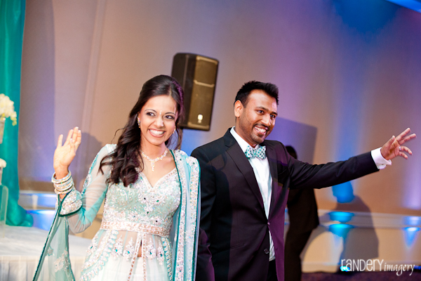 An indian bride and groom waves to family and friends at the Indian wedding reception.