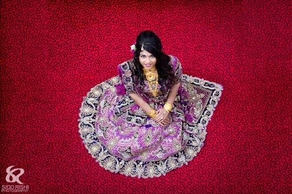 An Indian bride in a purple bridal lengha.