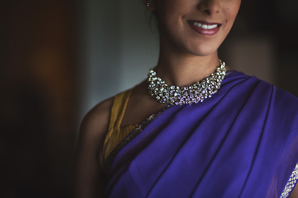 An Indian bridesmaid wears a purple sari and a gorgeous wedding necklace.