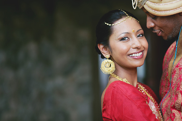An Indian bride smiles at her fusion Indian wedding.
