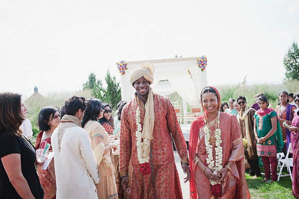 An Indian bride and groom are all smiles as they leave their Indian wedding ceremony.