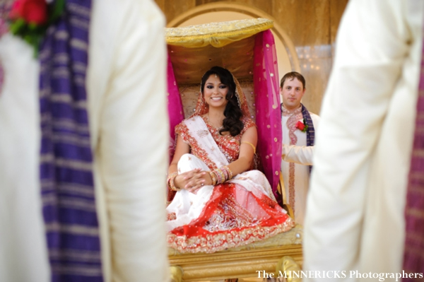 An Indian bride enters her indian wedding on a palanquin.
