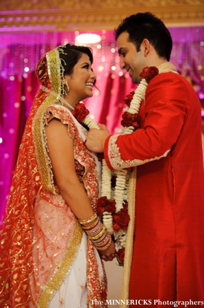 an indian bride and groom in traditional hindu wedding outfits.