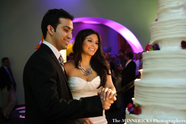 Indian bride and groom cut into indian wedding cake.