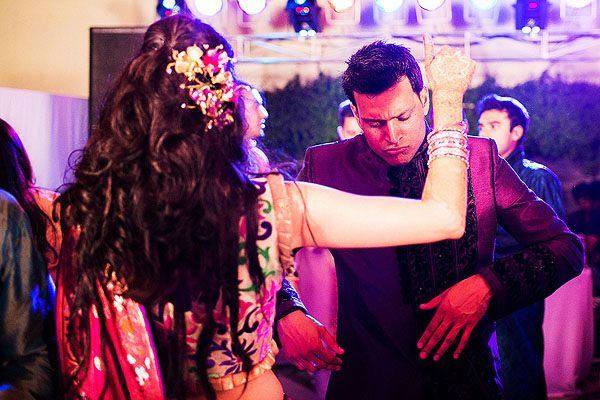 An Indian bride and groom dance at the outdoor sangeet in Udaipur, India.