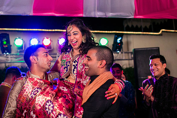 Indian wedding guests hoist up the Indian bride at her sangeet.