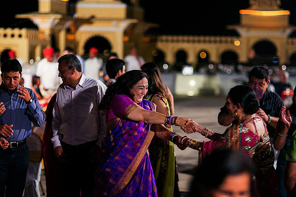 Family members in colorful saris dance at this Indian wedding welcome dinner.