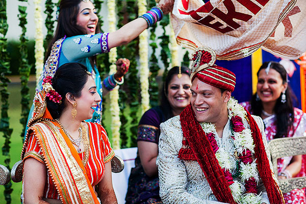 The groom sees his Indian bride for the first time in her bridal outfit.