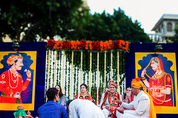 This Indian wedding altar is decorated with large paintings and flower garlands.