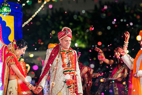 An Indian bride and groom are covered in confetti as they become husband and wife.
