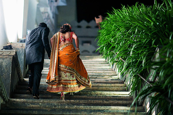 An Indian bride and groom enter their Indian wedding reception in Udaipur, India.