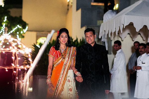 An Indian bride in an orange bridal lengha enter her modern Indian wedding reception.