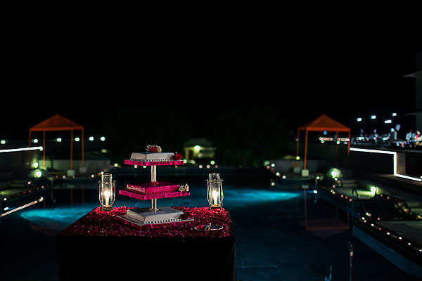 An Indian wedding cake overlooks this outdoor Indian wedding reception.