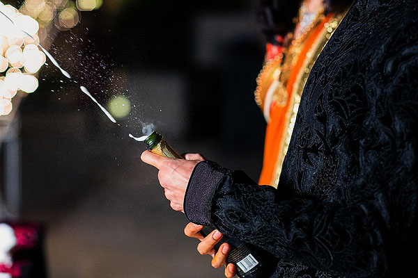 A groom pops open the champagne at his Indian wedding reception.