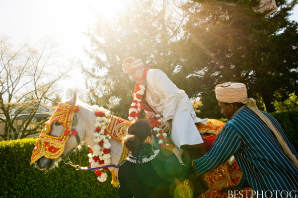 A groom gets on a horse to arrive to his Indian wedding.