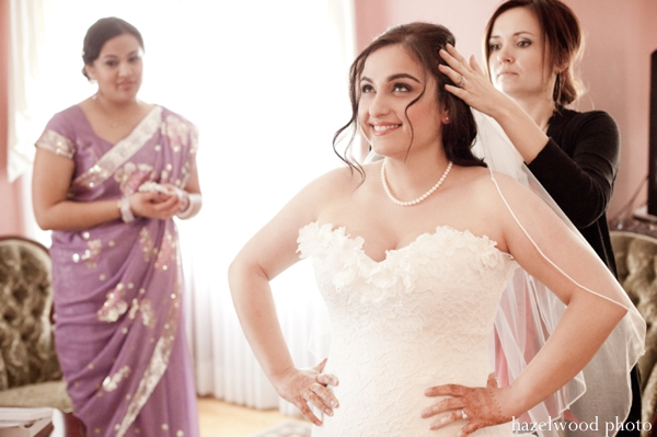 Indian bride slips on a white wedding gown for her fusion Indian wedding.