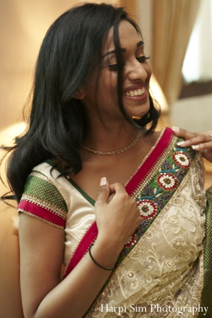 Indian bride puts on her bridal sari in green and red.