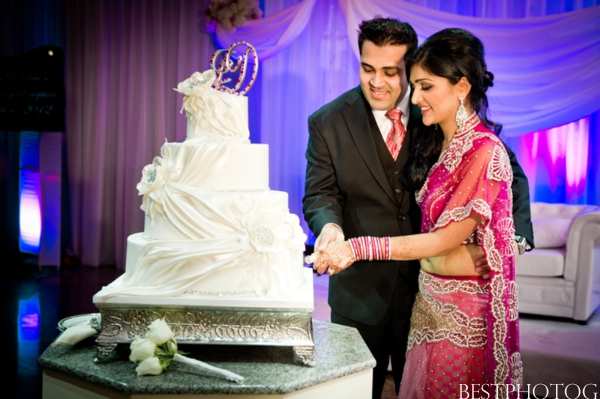 An Indian bride and groom cut into their Indian wedding cake.