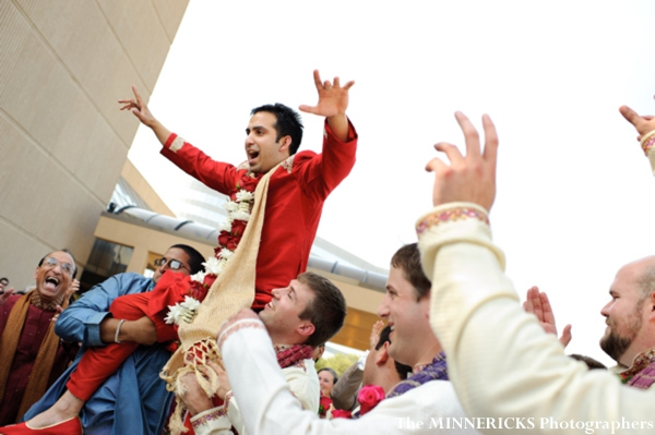 A groom is hoisted on top of shoulders as he arrives to his indian wedding ceremony.
