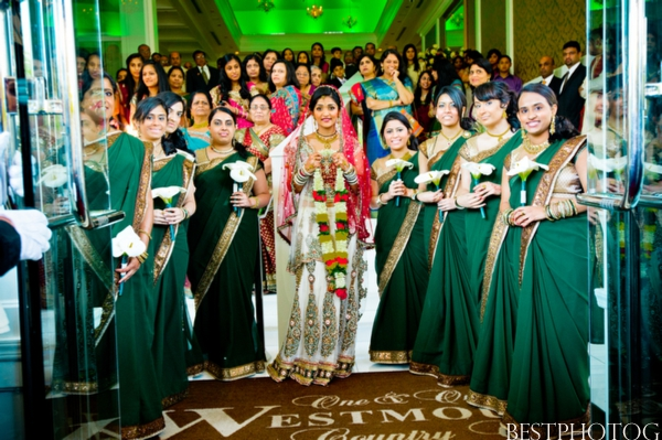 An Indian bride and her bridesmaid greet the groom at their Indian wedding ceremony.