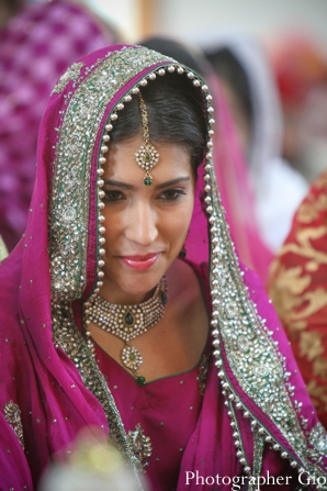Sikh Indian bride in hot pink sari at wedding ceremony.