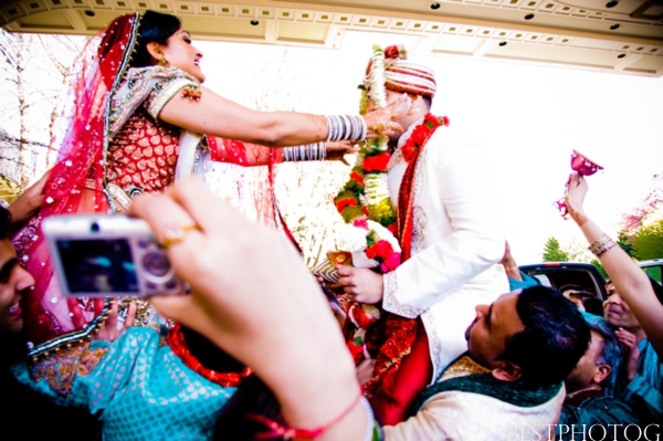 Indian wedding photography captures an Indian bride crowning her groom with a flower garland.