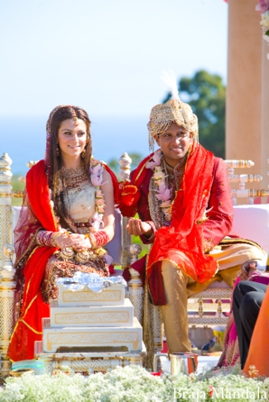 An Indian bride and groom in traditional indian wedding outfits.