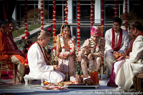 An Indian bride and groom are married at an outdoor Indian wedding ceremony.