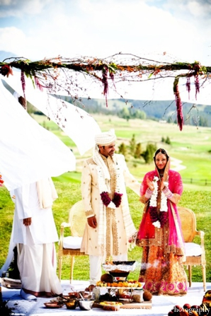 Indian bride and groom stand under an outdoor mandap.