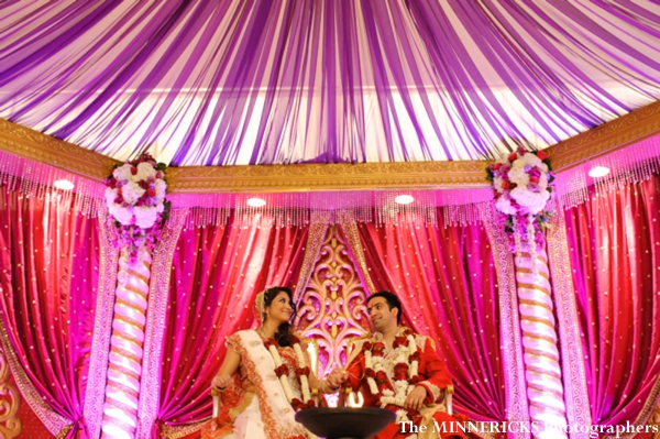 An indian bride and groom sit under a modern mandap.