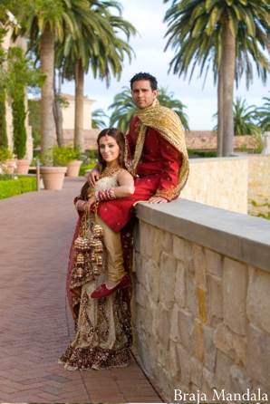Indian bride and groom post for outdoor indian wedding photography.