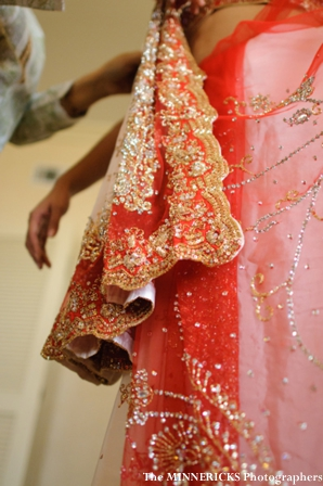 An indian bride is wrapped in a bridal lengha.