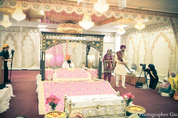 A SIkh indian wedding altar under a black pillar mandap.