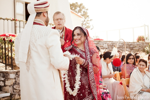 An Indian bride puts a jaimala flower garland on her groom.