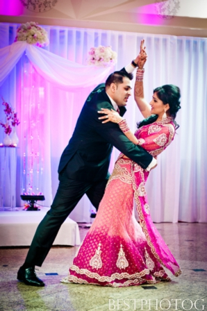 An Indian bride and groom have their first dance at their Indian wedding reception.