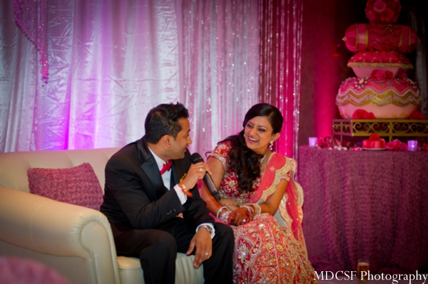 Indian bride and groom sit on pink themed Indian wedding altar.