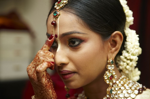 Indian bride receives turmeric to her face during her Indian wedding ceremony.
