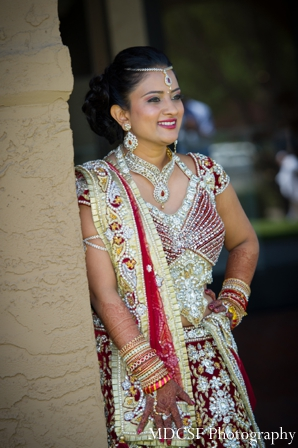 Indian bride poses in traditional bridal lengha.
