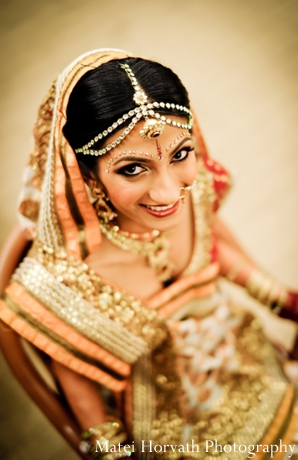 Indian wedding photography captures an Indian bride in gold bridal jewelry.