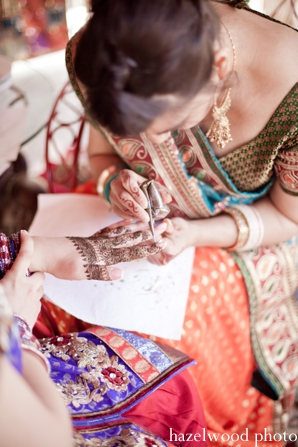 An Indian bride gets bridal mehndi before her fusion Indian wedding.