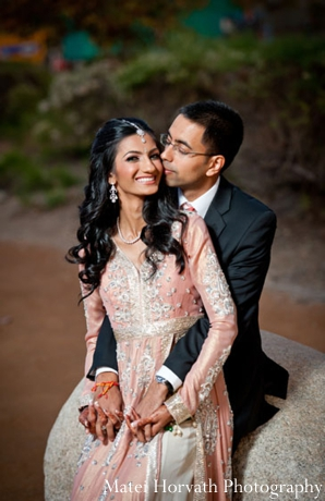 An Indian bride wears a pink Indian wedding outfit with traditional Indian bridal jewelry.