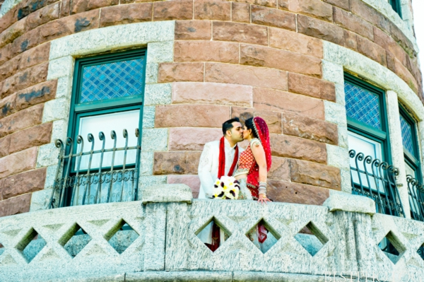 An Indian bride and groom kiss in this Indian wedding portrait.