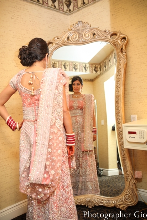 An Indian bride wears a baby pink lengha for her Indian wedding reception.