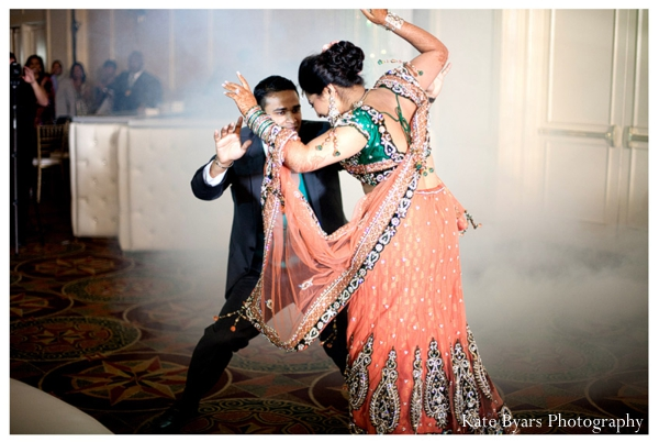 Indian bride dances with groom in a bridal lengha at her indian wedding reception.