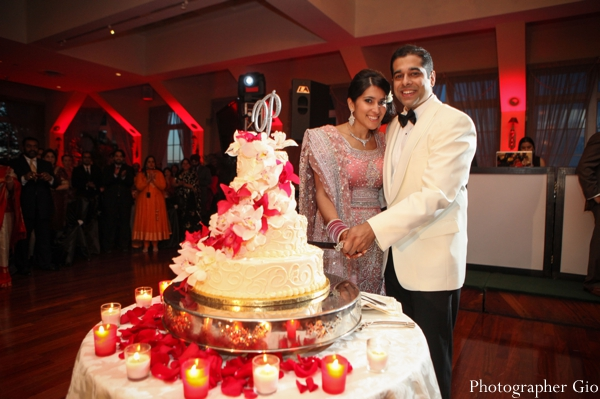 An indian bride and groom pose with their indian wedding cake in white and red.